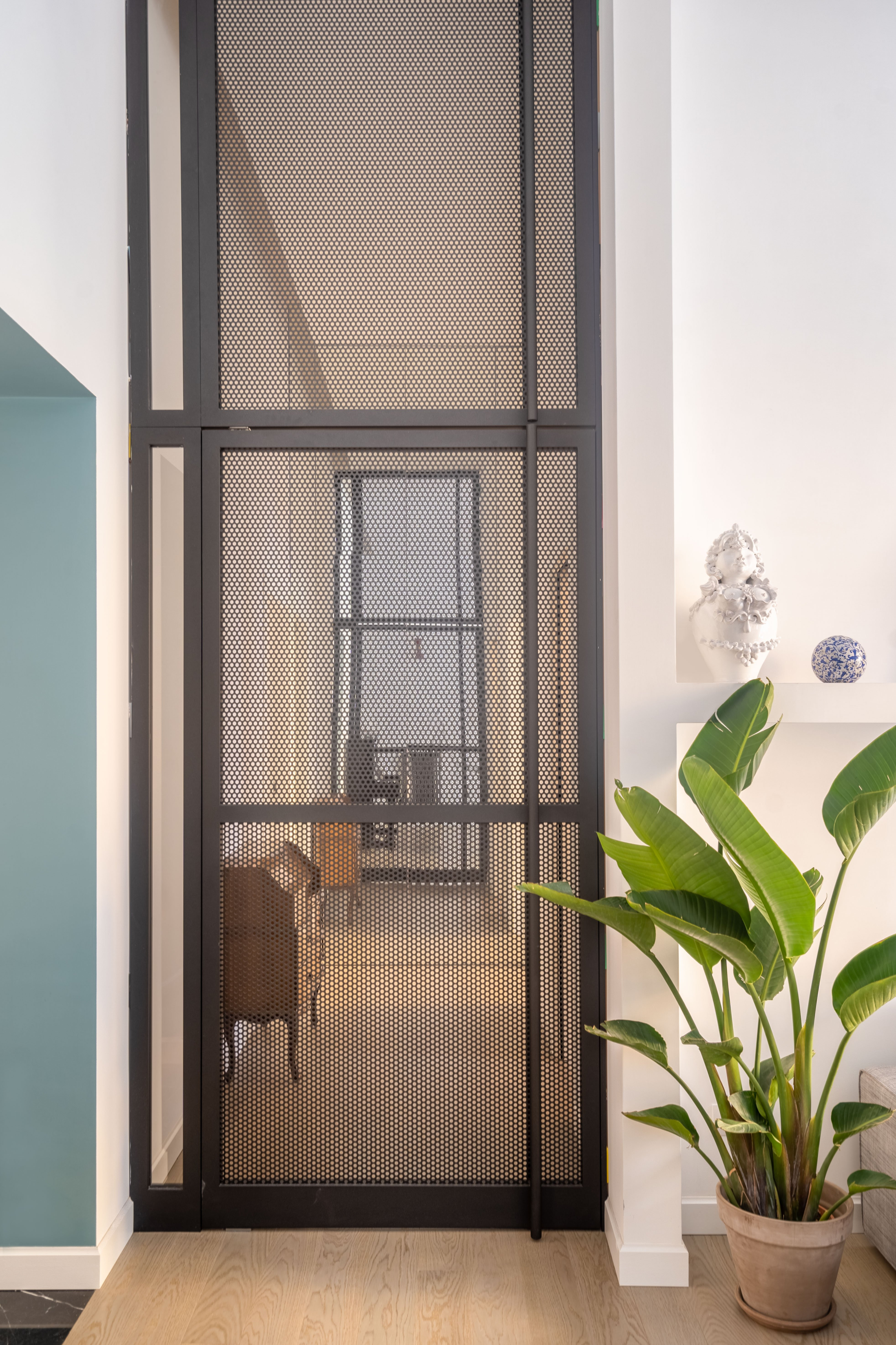 Statement interior pivot door from perforated steel. By Studio Tamat, with FritsJurgens System M pivot hinge