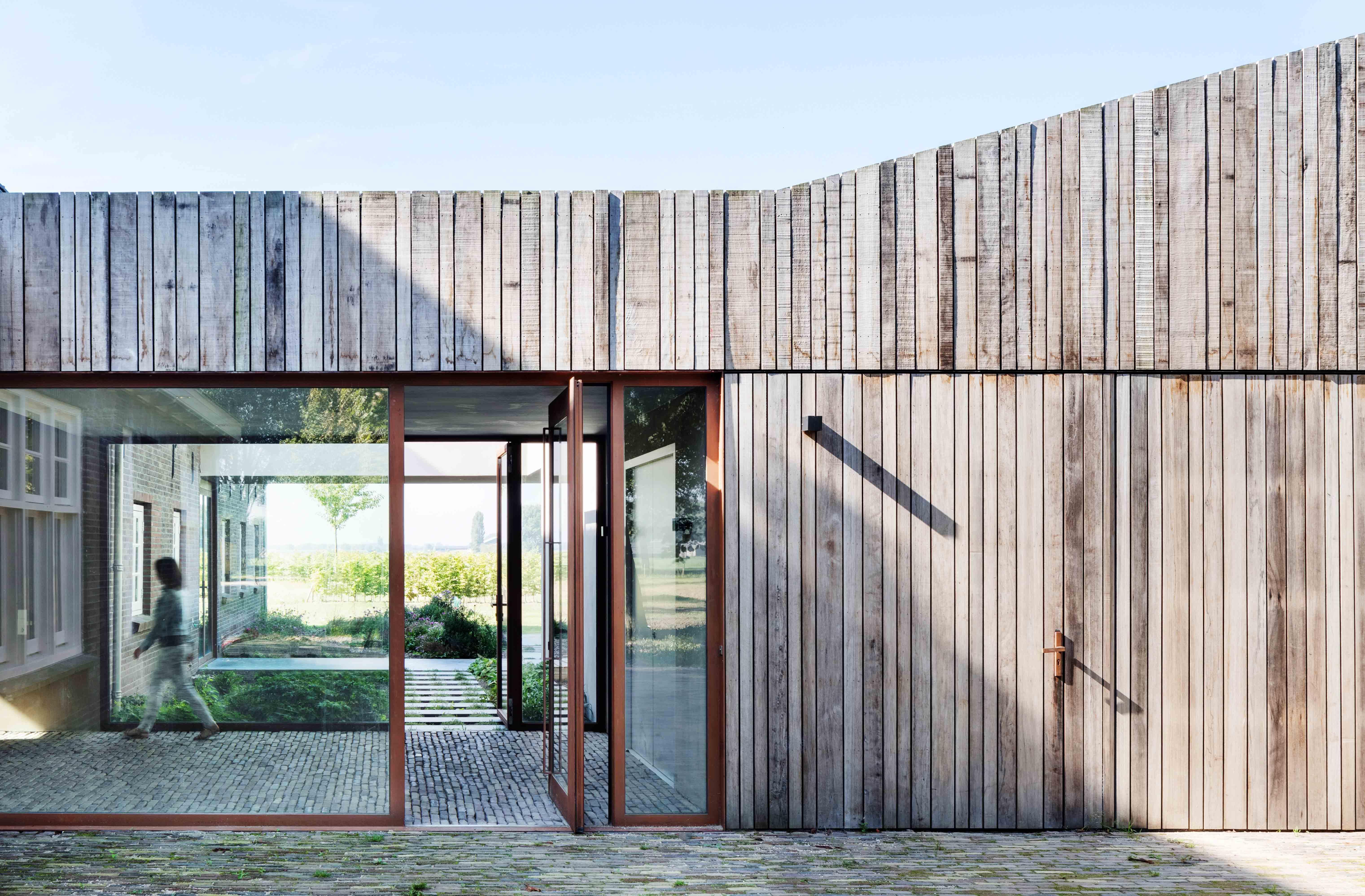 Just a little bit different – a copper-colored frame on a glass exterior pivot door. Design by Jeroen van Zwetselaar. FritsJurgens System M pivot hinge.