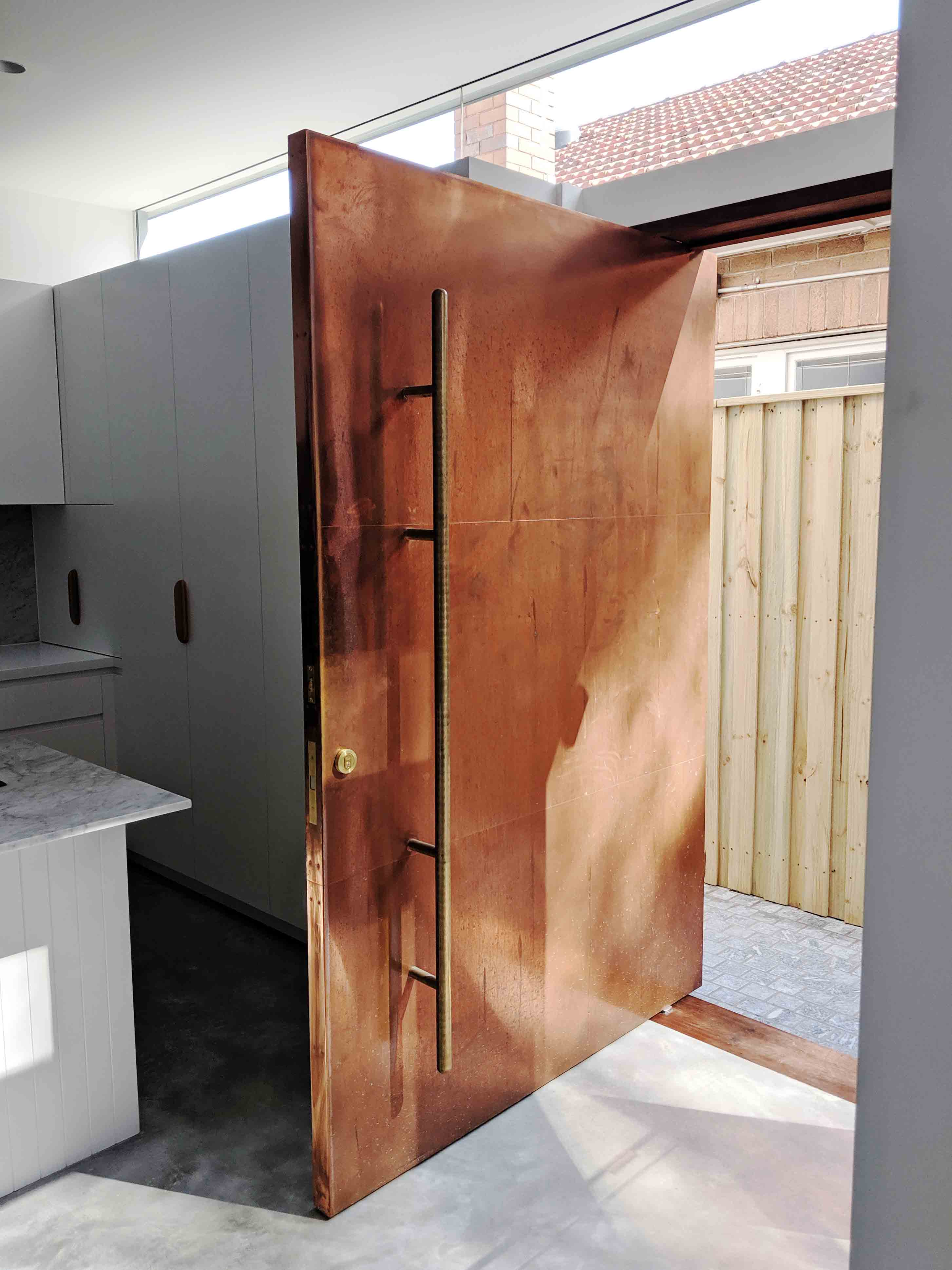 This entrance pivot door is clad with copper, which's rustic look will change over time. Design by Coppice Joinery. FritsJurgens System M pivot hinge.