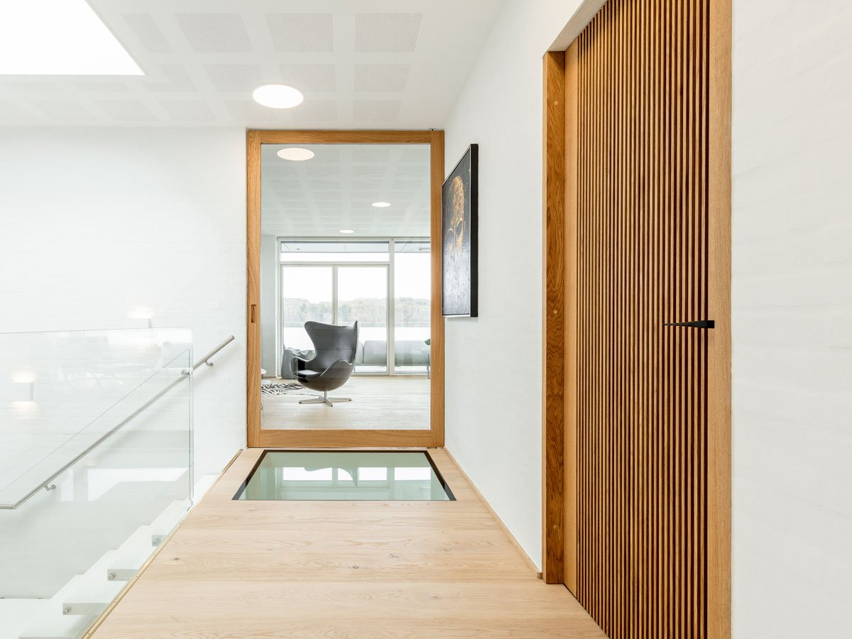 Glass and wood can be a beautiful, warm combination. The pivot hinge is hidden inside the door, which keeps the focus on the design. Design by Vahle Doors. FritsJurgens System M pivot hinge.